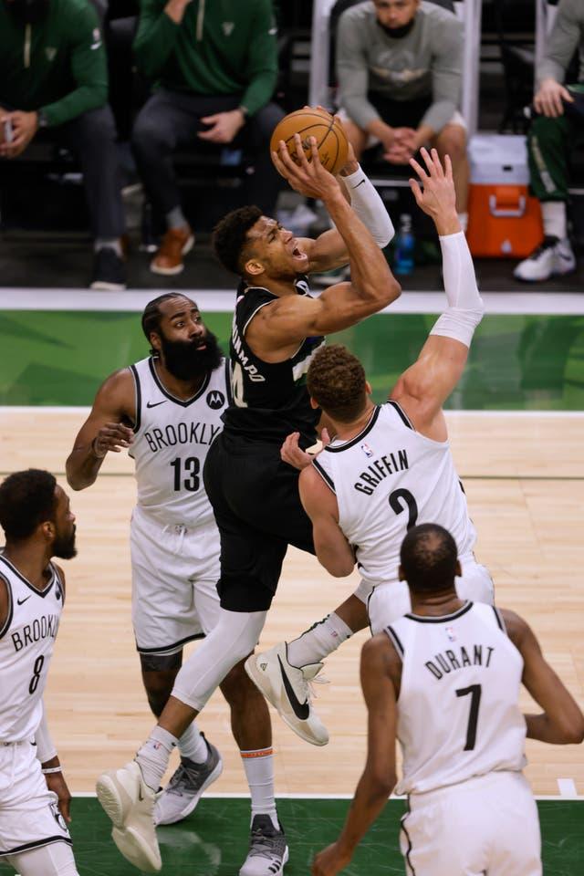 Milwaukee Bucks forward Giannis Antetokounmpo drives between Brooklyn Nets' James Harden and Blake Griffin