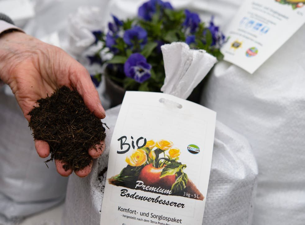 <p>File  A sales assistant shows organic flower soil at the biannual gardeners' market at the Botanical Gardens on April 5, 2014 in Berlin</p>