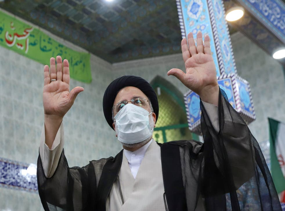 <p>Presidential candidate Ebrahim Raisi gestures after casting his vote</p>