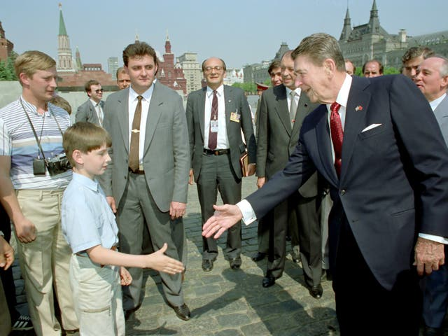 <p>Ronald Reagan extends his hand to a boy as Mikhail Gorbachev (R) looks on during a tour of Moscow's Red Square - could it also show a young Vladimir Putin (left, with camera) posing as a tourist?</p>