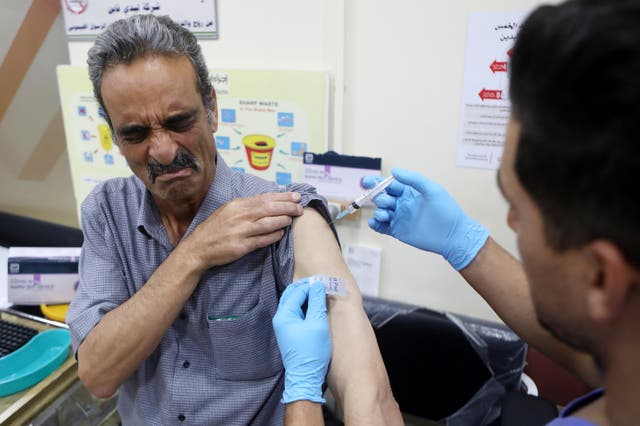 <p>A Palestinian medical worker receives a Covi-19 vaccine at the Palestinian Red Crescent Hospital in the West Bank city of Hebron</p>