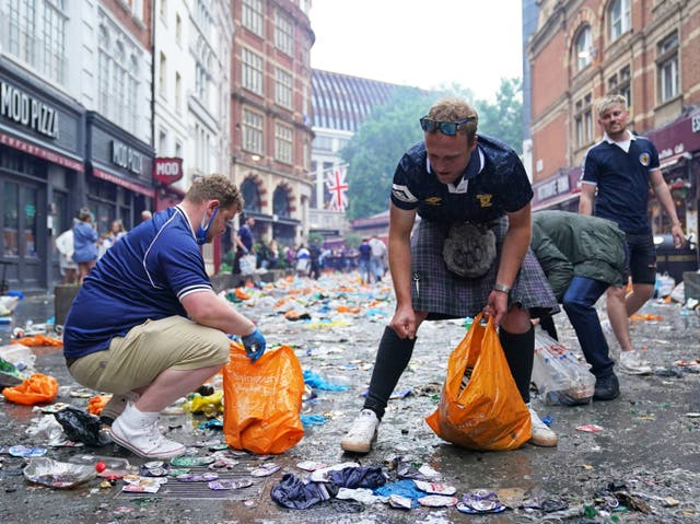 <p>Scotland fans clean up litter in Irving Street  near Leicester Square, London.</p>