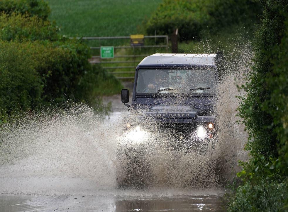 <p>A car drives through a flooded road near Chesham, Buckinghamshire</p>