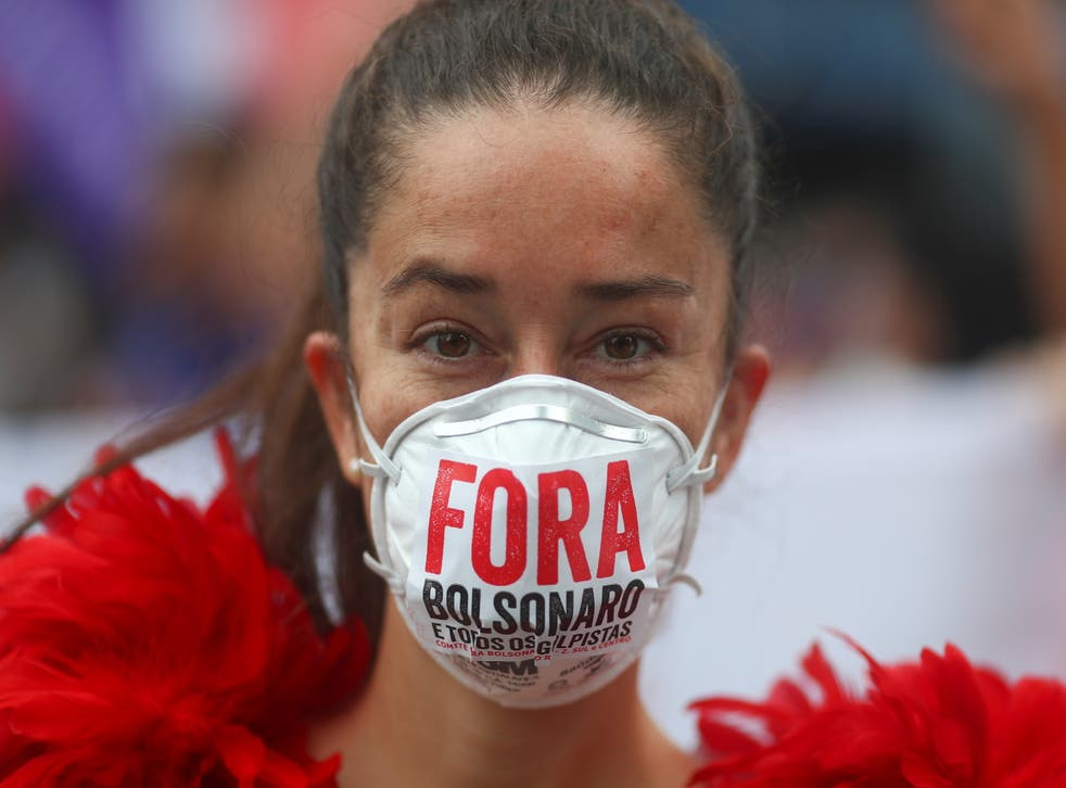 <p>'Fora Bolsonaro' ('Bolsonaro out'): A woman protests against Brazil's President Jair Bolsonaro's handling of Covid-19 </p>