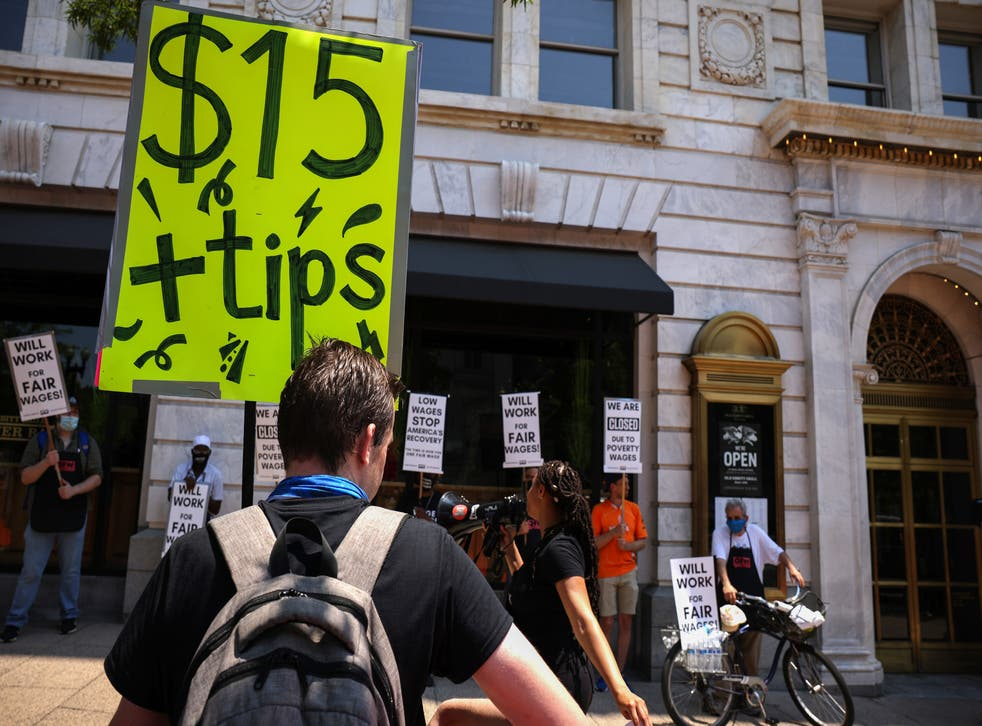 """<p>An activist holds a sign up outside Old Ebbitt Grill restaurant during a """"Wage Strike"""" demonstration on May 26th, 2021 in Washington, DC. Delaware lawmakers have voted to give final approval to raising the state's minimum wage to $15 an hour.</p>"""