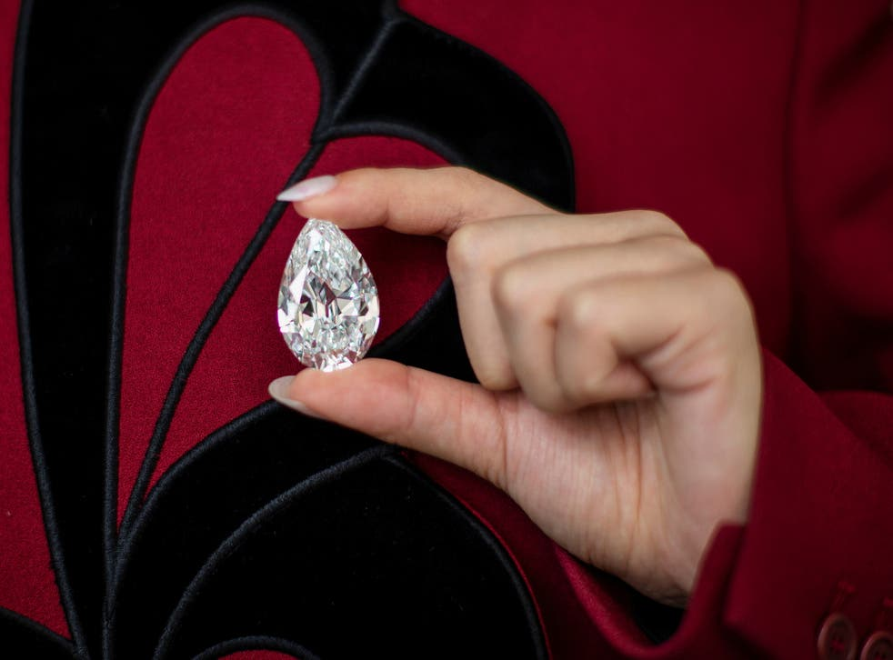 <p>An employee of Sotheby's poses with a rare pear-Shaped D Colour Flawless 100+ carat diamond at Sotheby's in New York City, New York, US, 21 June, 2021</p>
