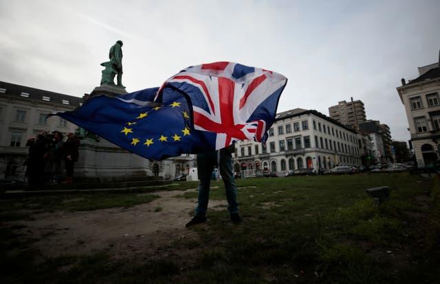 <p>A man unfurls a Union and EU flag outside the European Parliament in Brussels</p>