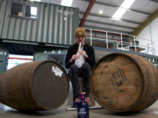 <p>Ali Levack plays the tin whistle to casks of whisky</p>