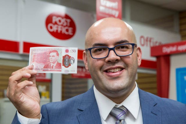 Postmaster Ahmed Butt holding the new £50 banknote