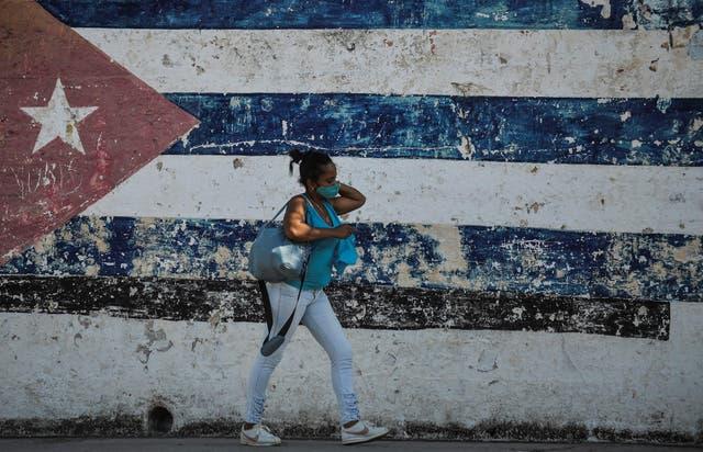 <p>A woman walks near a wall depicting the Cuban flag in Havana as the UN meets in New York</p>