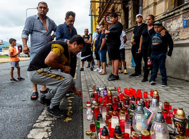 <p>A manlights a candle on Tuesday in Teplice, Czech Republic, in the place where a Roma man died in an ambulance after a police action on Saturday</p>
