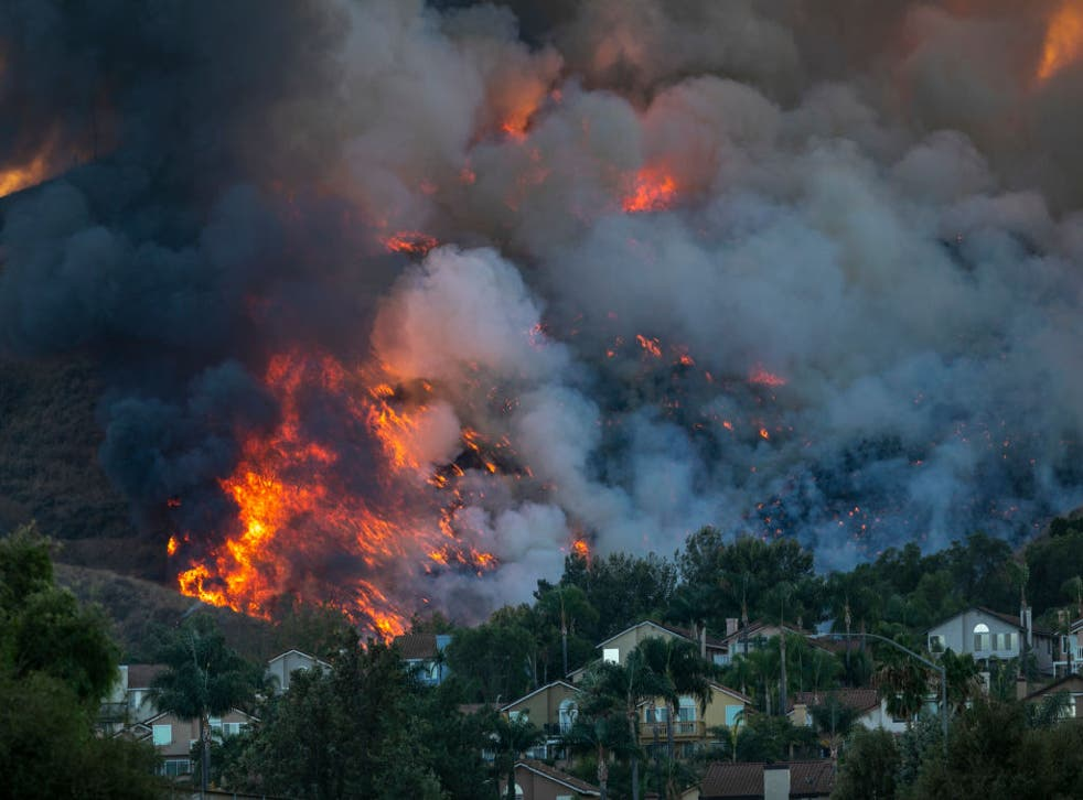 <p>Flames rise near homes during the Blue Ridge Fire on October 27, 2020 in Chino Hills, California</p>