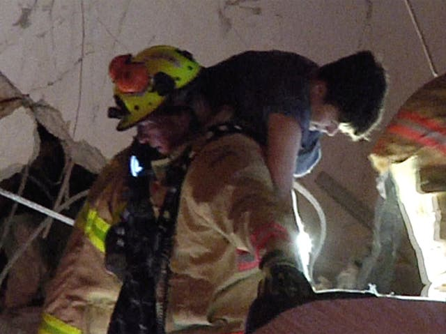 This photo taken from video provided by ReliableNewsMedia, firefighters rescue a survivor from the rubble of the Champlain Towers South Condo after the multistorey building partially collapsed in Surfside, Fla