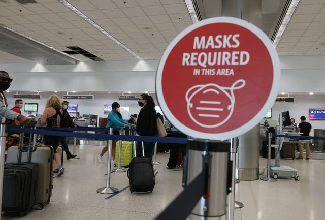 <p>A sign reading, 'masks required in this area,' is seen as travelers prepare to check-in for their Delta airlines flight at the Miami International Airport on February 01, 2021 in Miami, Florida</p>