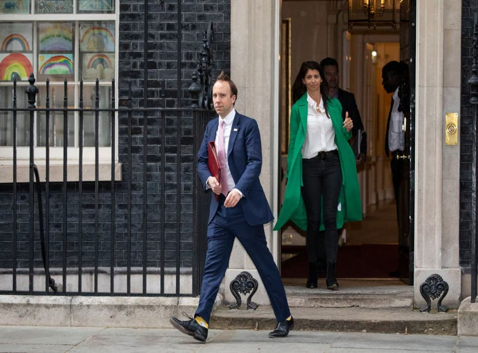 <p>Matt Hancock leaves 10 Downing Street after the daily press briefing in May, with Gina Colandangelo in the green coat</p>