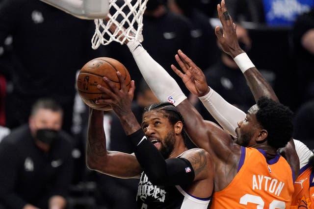 Los Angeles Clippers guard Paul George, left, shoots as Phoenix Suns centre Deandre Ayton defends