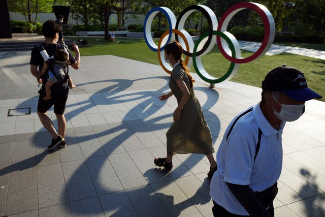 <p>People walking past the Olympic rings in Tokyo. The Japanese public has generally been opposed to the Games, partly over fears that coronavirus levels will spike as about 100,000 people enter the country</p>