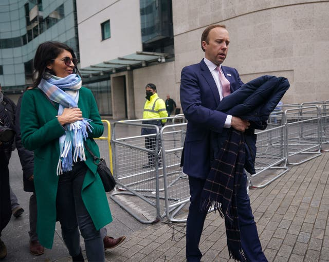 <p>Getting their coats: Gina Coladangelo pictured with Matt Hancock last month</p>