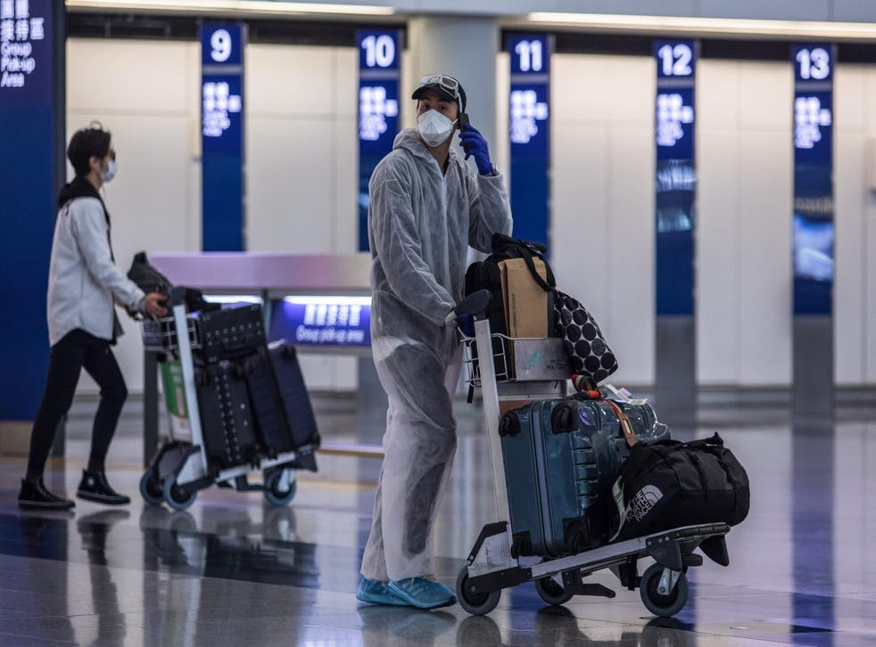 <p>File: A passenger wearing a face mask and protective suit at the Hong Kong International Airport on 4 April, 2020</p>