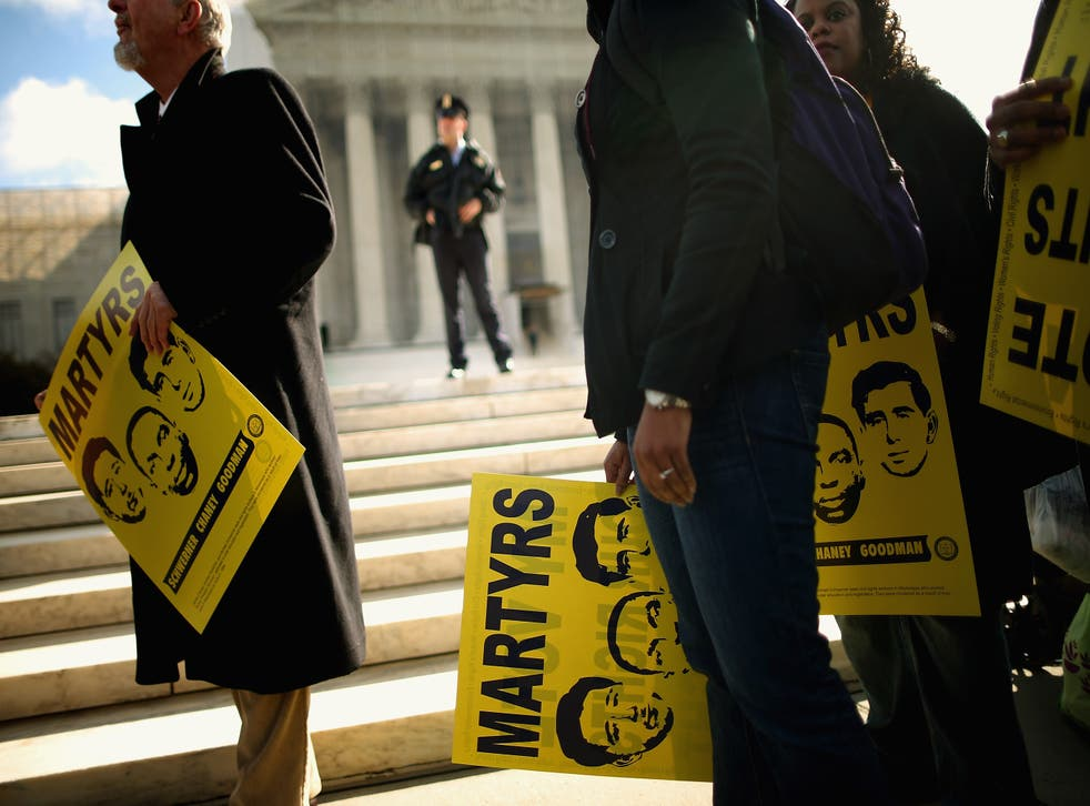 <p> Holding signs with images of murdered Mississippi civil rights workers James Earl Chaney, Andrew Goodman, and Michael Schwerner, demonstrators rally in front of the US Supreme Court on 27 February, 2013 in Washington, DC. Previously sealed files on the 1964 killings of the three men have been released for public viewing.</p>