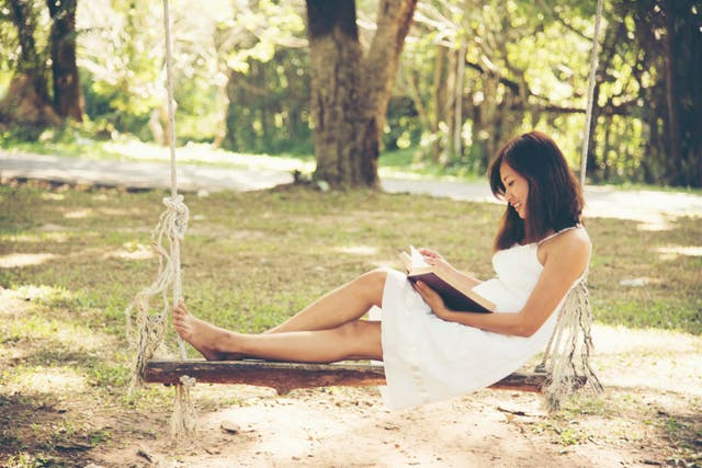 Woman sitting on a swing reading a book