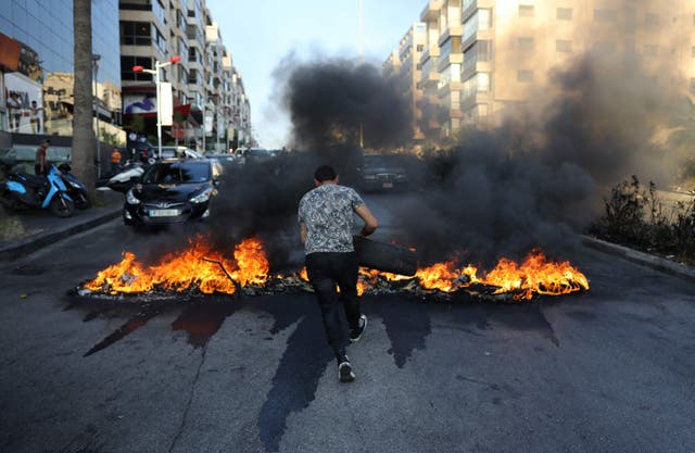 <p>A Lebanese man sets tires on fire during ongoing protests against fuel and energy shortages in Beirut</p>