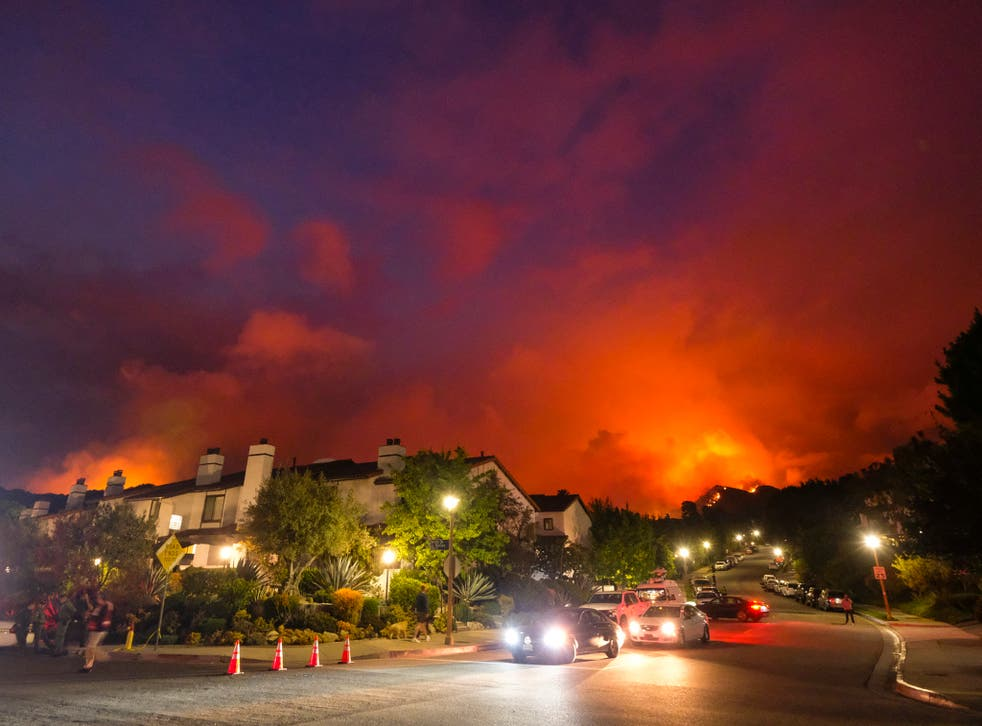 <p>Smoke rises behind homes in Pacific Palisades last month</p>