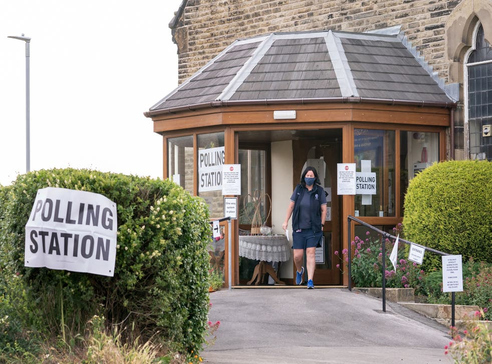 <p>A voter leaves Norristhorpe United Reformed Church polling station in the West Yorkshire constituency of Batley and Spen</p>