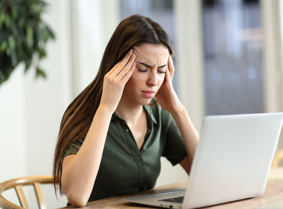 Stressed woman suffering migraine with a laptop sitting in a table at home