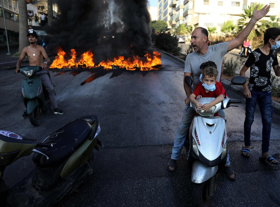 <p>A Lebanese man on a scooter with two children gestures near tires set on fire during a protest at a main road in Lebanon's capital Beirut against dire conditions amidst the ongoing economical and political crisis</p>