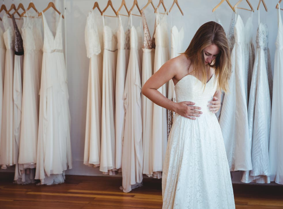 Woman trying on wedding dress in a shop