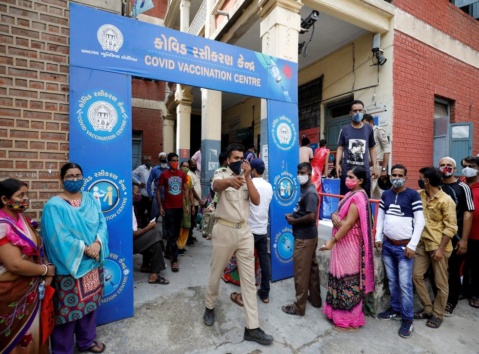 <p>A police officer manages people who came to receive a Covid-19 vaccine dose outside a centre in Ahmedabad on 30 June, 2021</p>