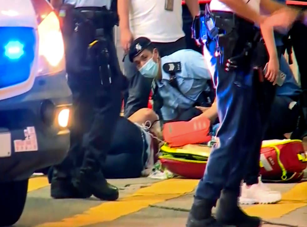 <p>In this image from video provided by TVB, a police officer on the ground receives medical treatment after being stabbed by a man on a street in Causeway Bay of Hong Kong, 1 July 2021</p>