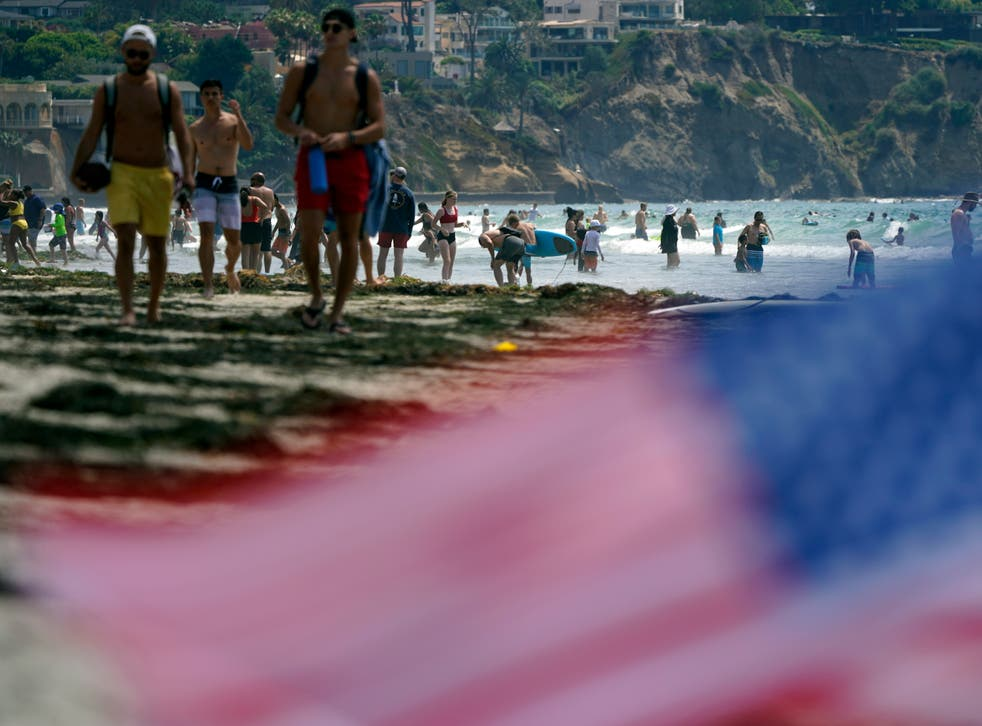 <p>FILE - In this July 1, 2021, file photo, people walk along La Jolla Shores beach as Independence Day weekend nears in San Diego. Americans enjoying newfound liberty are expected to travel and gather for cookouts, fireworks and family reunions over the Fourth of July weekend in numbers not seen since pre-pandemic days. (AP Photo/Gregory Bull, File)</p>