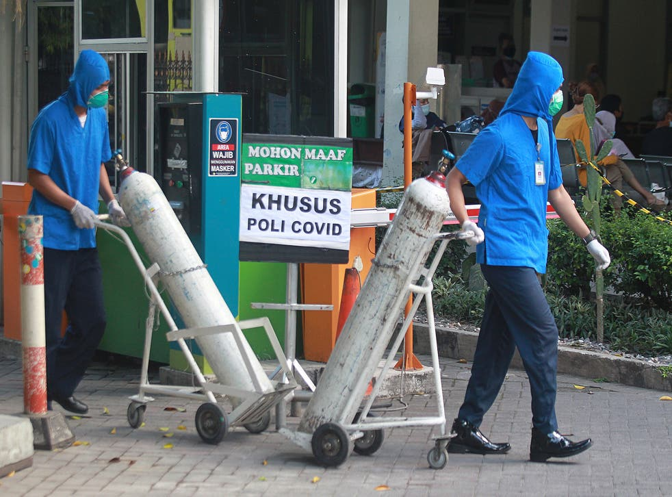 <p>Medical workers wheel oxygen tanks at Dr Sardjito Central Hospital in Yogyakarta, Indonesia, after a number of Covid-19 patients died amid an oxygen shortage at the hospital following a nationwide surge of coronavirus infections</p>