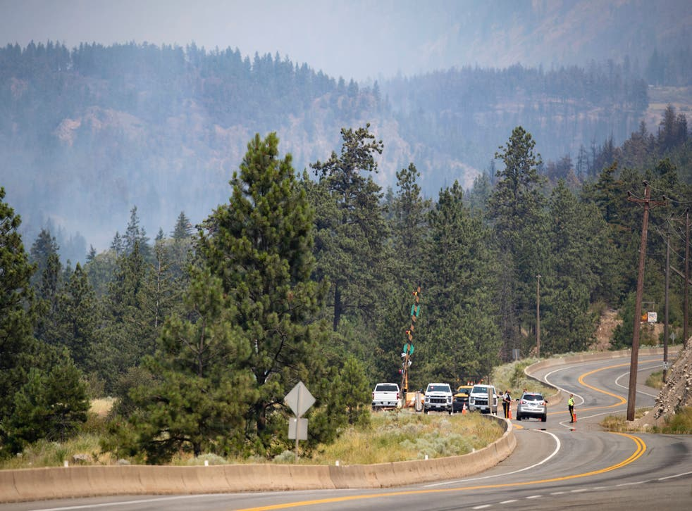 <p>Royal Canadian Mounted Police (RCMP) officers man a roadblock on the Trans-Canada Highway as a wildfire burns in Lytton, British Columbia, Friday, July 2, 2021. Officials on Friday hunted for any missing residents of a British Columbia town destroyed by wildfire as Canadian Prime Minister Justin Trudeau offered federal assistance. </p>