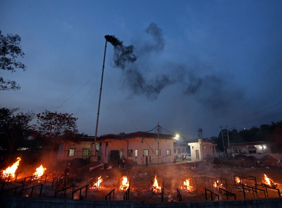 <p>File: Smoke billows from a chimney of an electric crematorium as burning pyres of Covid-19 victims are seen at a crematorium in Bhopal on 23 April, 2021</p>