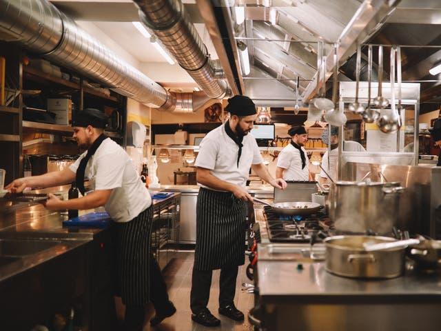 <p>Equipo de cocina de restaurante preparando comida</p>