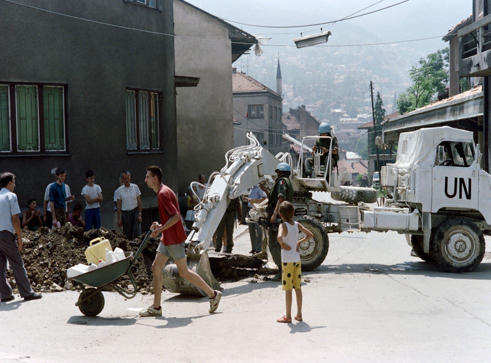 <p>A man carrying jerrycans passes by a UN bulldozer in the streets of Sarajevo during the Bosnian war</p>