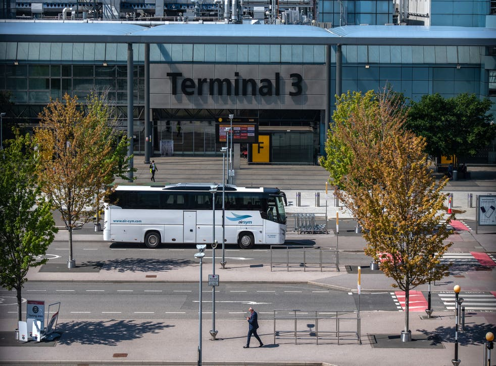 <p>A bus used to transport red list arriving airline passengers passes the Terminal 3 building at Heathrow Airport </p>