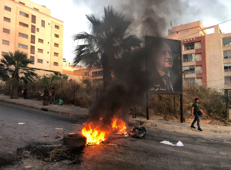 <p>A man walks near a burning fire blocking a road during a protest against mounting economic hardships in Beirut</p>