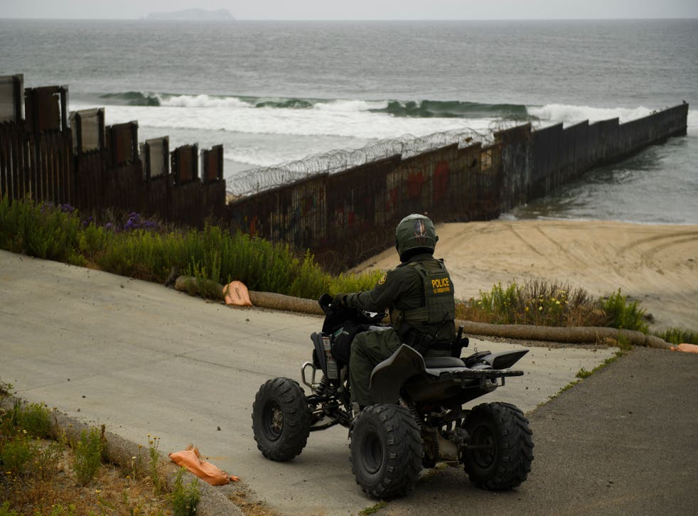 <p>A US Border Patrol agent patrols on an all-terrain vehicle where the border wall ends in the Pacific Ocean along the US-Mexico border between San Diego and Tijuana, during a tour with the US Customs and Border Protection on May 10, 2021 at International Friendship Park in San Diego County, California.</p>