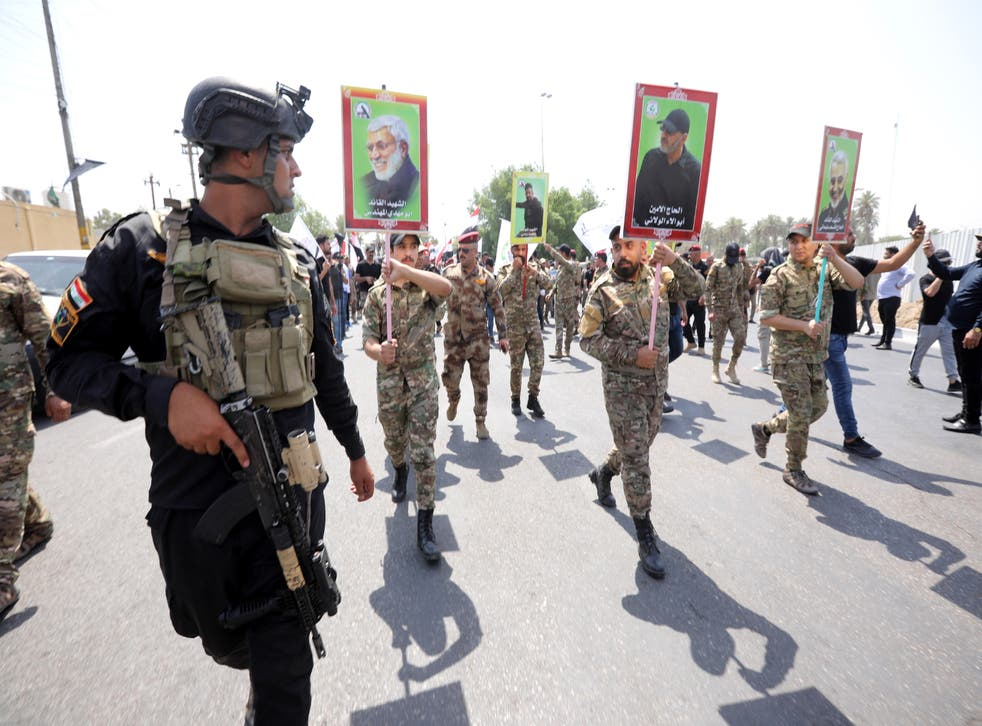 <p>Supporters of Iran-backed Iraqi Shiite Popular Mobilization Forces carry the pictures of their comrades who were killed in a US airstrike near the Iraqi border last month</p>
