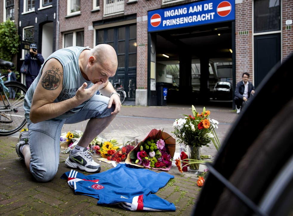 <p>A man pays tribute to Dutch crime reporter Peter R de Vries in the Lange Leidsedwarsstraat in Amsterdam</p>