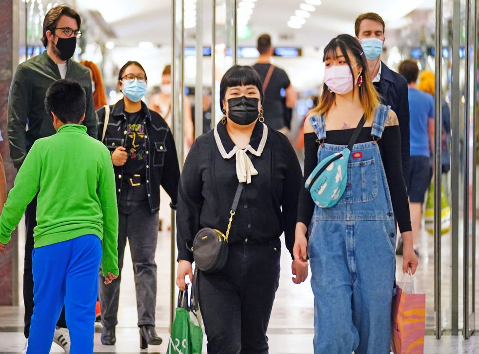 <p>Shoppers wearing facemasks in east London on Wednesday as daily Covid cases rose to more than 32,000</p>