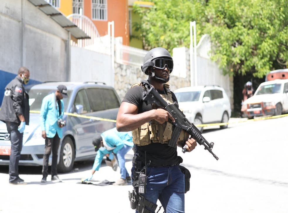 <p>Members of the Haitian police and forensics look for evidence outside of the presidential residence </p>