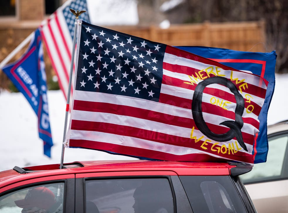 <p> A car with a flag endorsing QAnon drives by outside the Governor's Mansion on 14 November 2020 in St Paul, Minnesota</p>