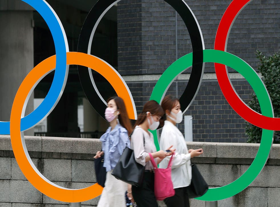 <p>People wearing face masks walk past the Olympics Rings statue in Tokyo on 8 July 2021</p>