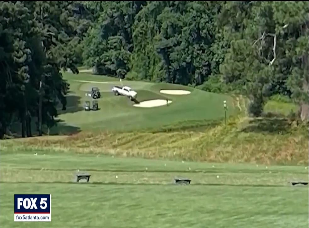 <p>The white pickup truck on the tenth hole at Pinetree Country Club golf course in Georgia, where three bodies were found on 3 July 2021.</p>
