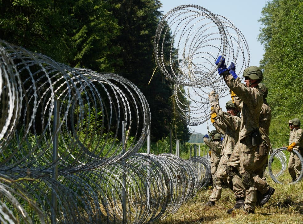 <p>Lithuanian soldiers install razor wire on border with Belarus in Druskininkai</p>
